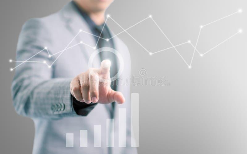在灰色衣服的商人指向他的手指的和接触有信息图表的屏幕 免版税库存照片