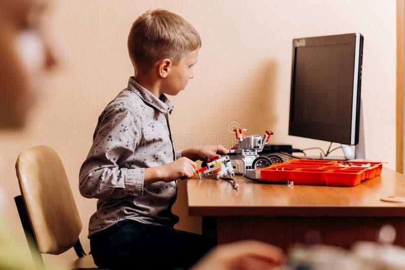 在灰色衬衣打扮的努力男孩由机器人建设者做一个机器人在有计算机的书桌在学校  库存图片