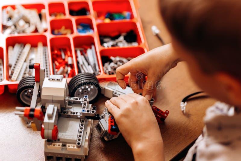 在灰色衬衣打扮的勤奋男孩由机器人建设者做一个机器人在书桌在机器人学学校  库存照片