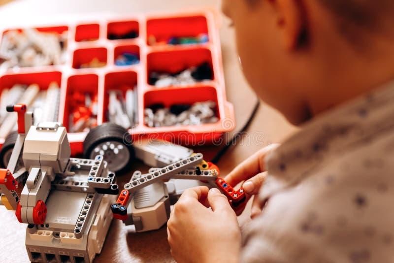 在灰色衬衣打扮的聪明的男孩由机器人建设者做一个机器人在书桌在机器人学学校  库存图片