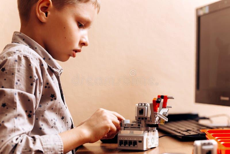 在灰色衬衣打扮的聪明的男孩由机器人建设者做一个机器人在有计算机的书桌在学校  免版税库存照片