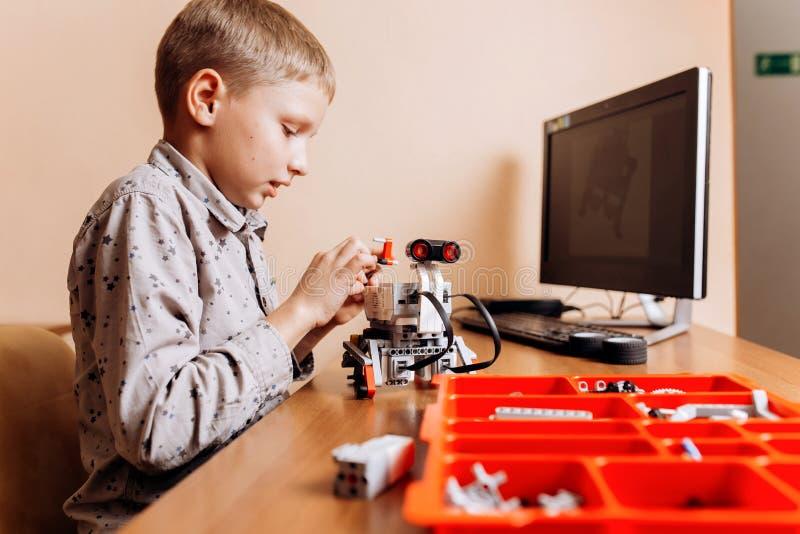 在灰色衬衣打扮的聪明的男孩由机器人建设者做一个机器人在有计算机的书桌在学校  免版税库存图片