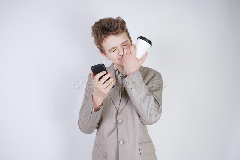 在灰色西装的青少年白种人学生身分,叫由智能手机,饮用的咖啡,接触他鼻子和说谎 库存照片