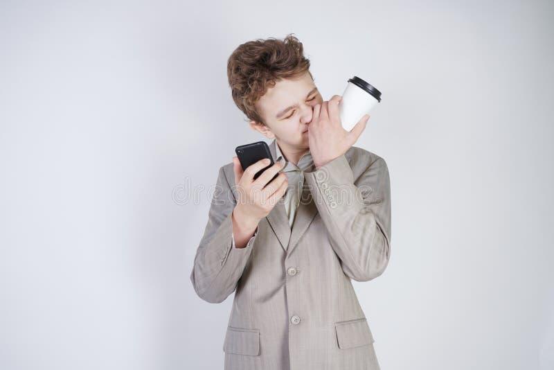 在灰色西装的青少年白种人学生身分,叫由智能手机,饮用的咖啡,接触他鼻子和说谎 图库摄影