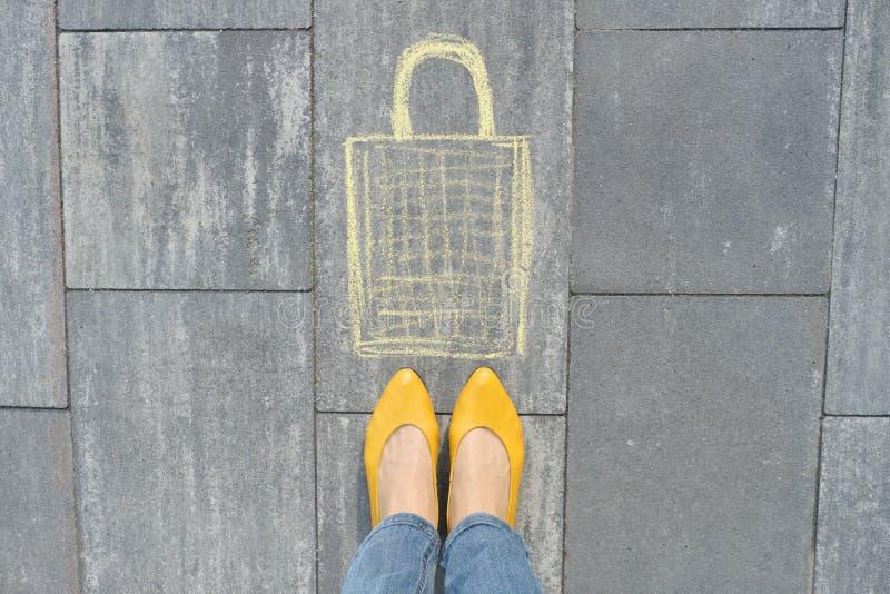 在灰色边路写的购物带来图片在有妇女腿的蜡笔在黄色鞋子 免版税库存照片
