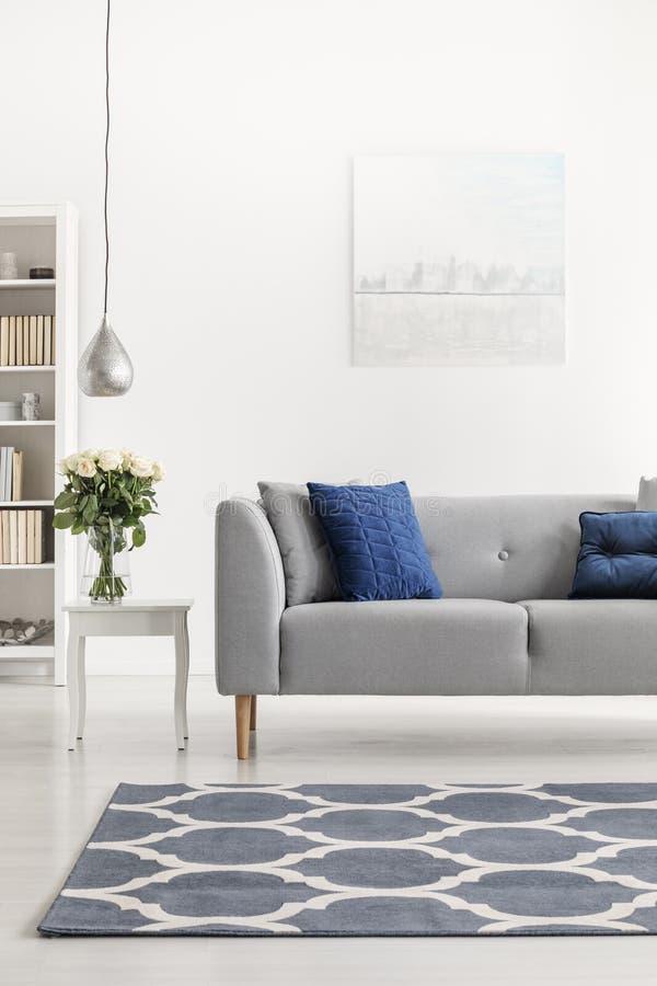在灰色长沙发前面的被仿造的地毯有蓝色枕头的在白色顶楼内部与花 实际照片 免版税库存图片