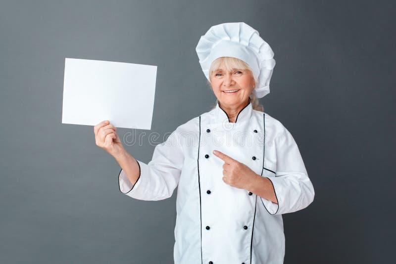 在灰色隔绝的资深妇女厨师演播室身分指向看照相机的纸愉快 免版税图库摄影