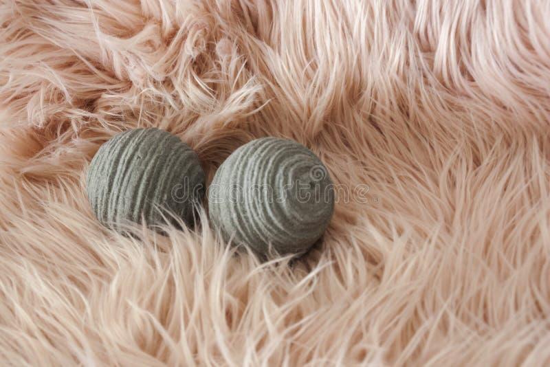 在灰色颜色的两个装饰球在桃红色头发背景 库存图片