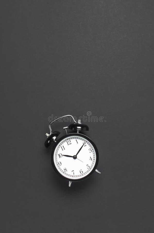 在灰色黑暗的背景顶视图平的被放置的拷贝空间的黑减速火箭的闹钟 Minimalistic背景,时间的概念 库存照片