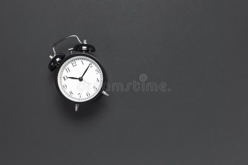 在灰色黑暗的背景顶视图平的被放置的拷贝空间的黑减速火箭的闹钟 Minimalistic背景,时间的概念 免版税库存照片
