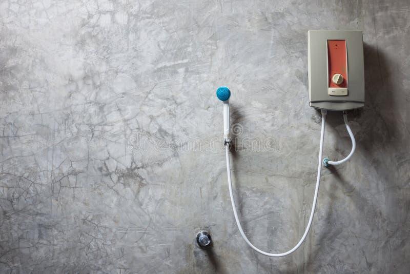 在灰色水泥墙壁上的水加热器在卫生间里 库存图片
