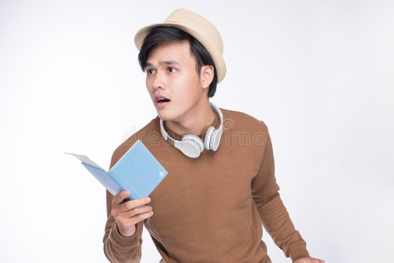 在灰色backgrou的惊奇的亚洲男性旅游举行的护照 免版税图库摄影