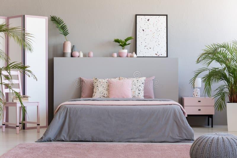 在灰色bedhead的海报在与桃红色枕头的卧室内部 免版税库存图片