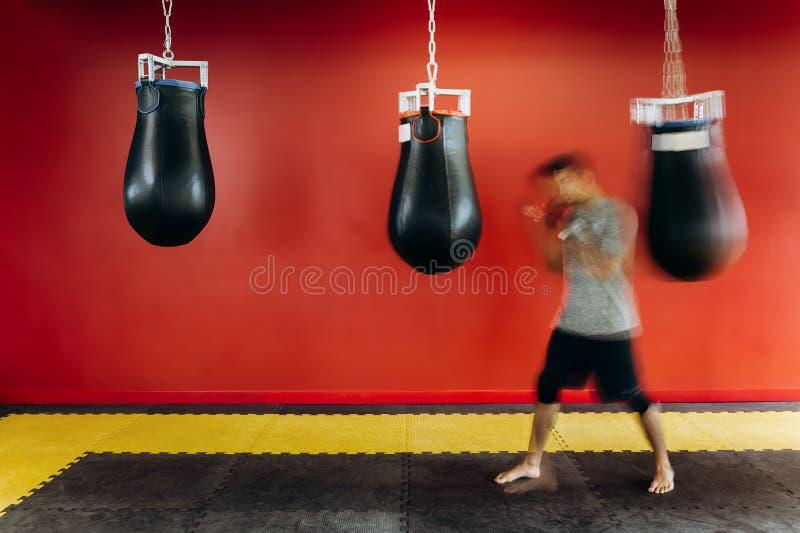 在灰色T恤杉和黑短裤打扮的人解决与一个黑吊袋对在健身房的红色墙壁 库存图片