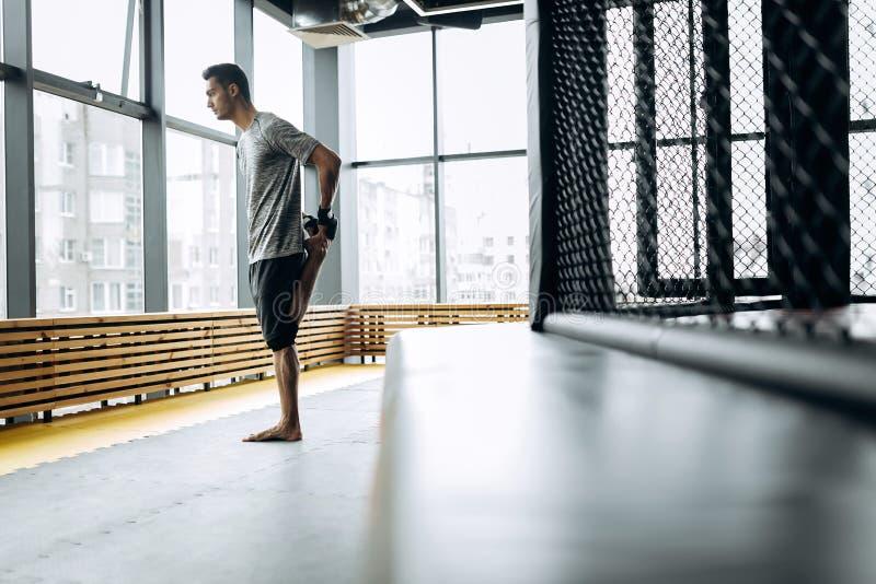 在灰色T恤杉打扮的人舒展他的在把装箱的健身房的胳膊与全景窗口 免版税图库摄影
