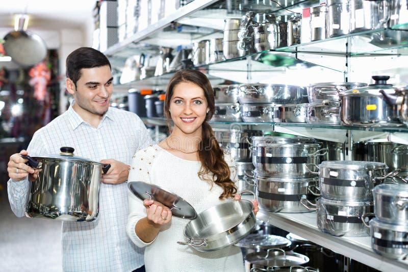 在炊具部分的微笑的愉快的美好的夫妇 免版税库存图片