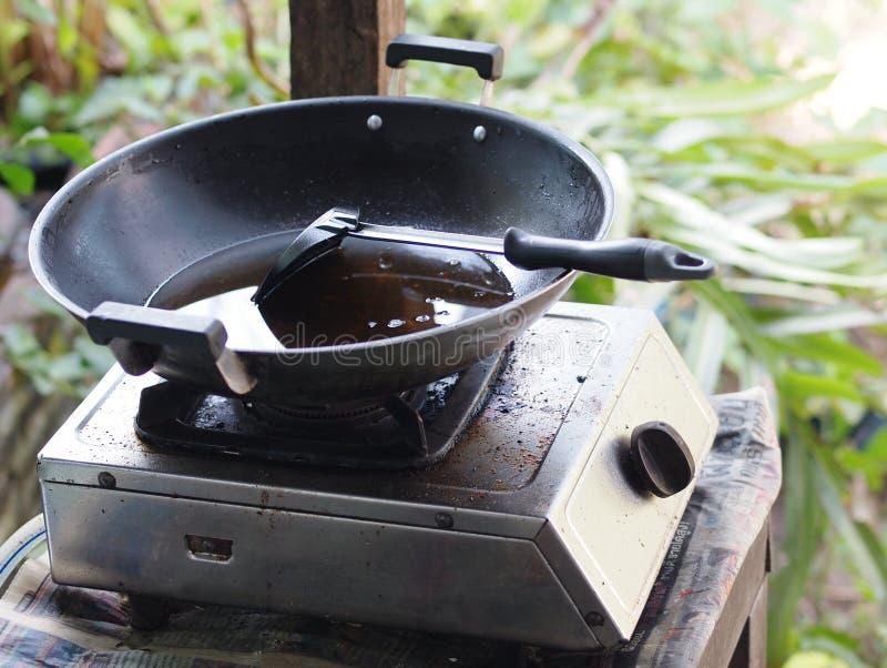 在炸锅的老使用的清楚的黄色油有大匙子的 免版税库存图片