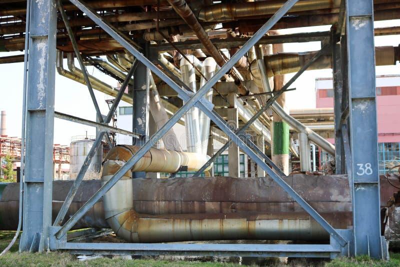 在炼油厂,石油化学制品,化学制品用管道运输estocada,管子有蒸汽的和凝析油,管道支架与蓝色射线 库存图片