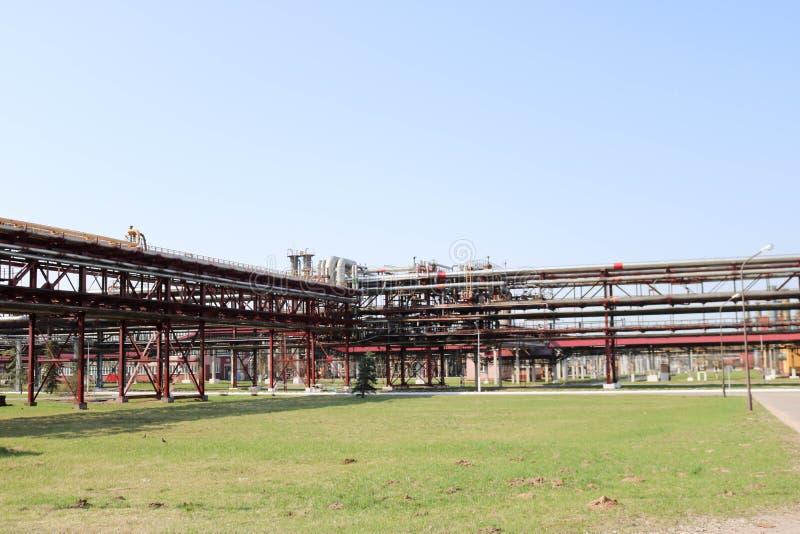 在炼油厂,石油化学制品,化工厂用管道运输与铁生锈的管子抽的液体的与出口和流失的天桥 库存照片