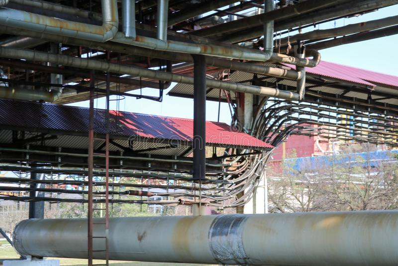 在炼油厂,石油化学制品, che用管道运输与铁生锈的管子的天桥抽的液体的,凝析油与出口和流失 免版税图库摄影