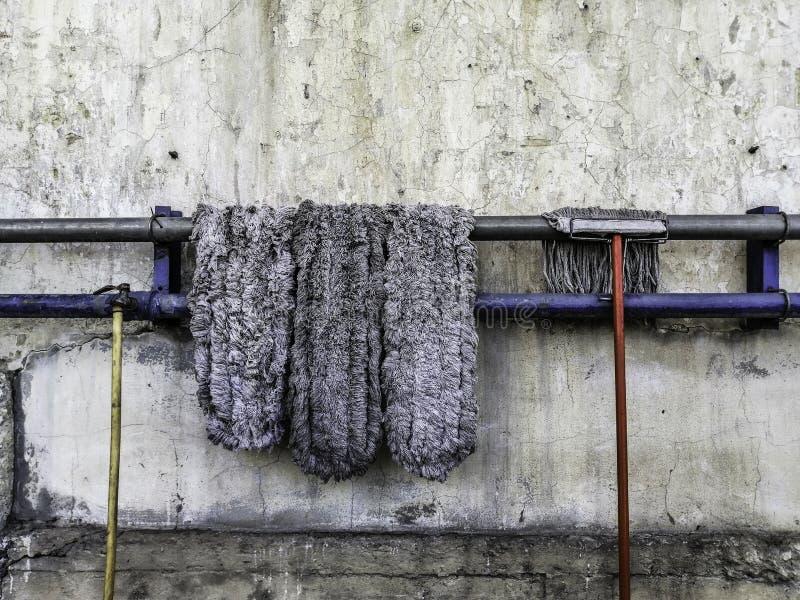 在烘干的钢路轨的老拖把位置,老龙头和老橡胶水管,老水泥墙壁背景 库存图片
