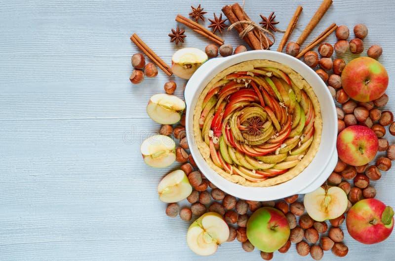 在烘烤盘的未煮过的苹果馅饼装饰用新鲜的切的苹果,榛子,肉桂条,茴香担任主角 素食饼 免版税图库摄影