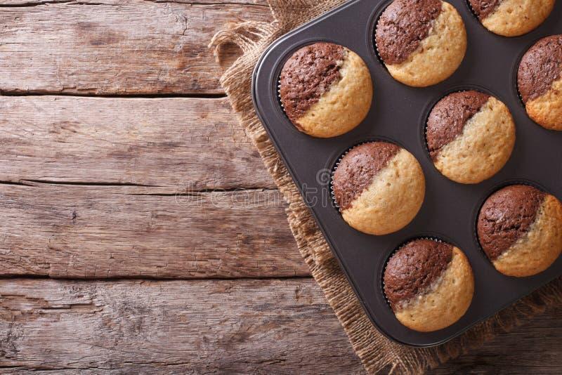 在烘烤盘的热的五颜六色的杯形蛋糕 水平的顶视图 库存图片