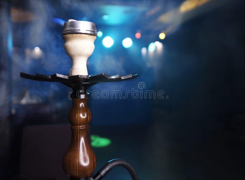 在烟云的水烟筒在被弄脏的蓝色背景的特写镜头与bokeh 库存照片