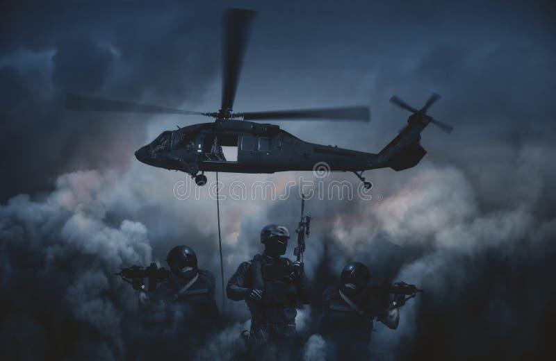 在烟和火之间的军用直升机 库存照片