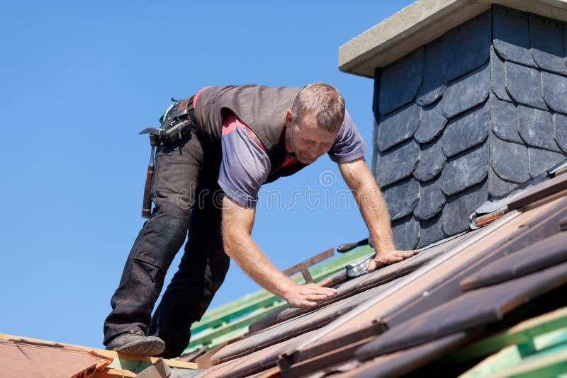 在烟囱旁边的盖屋顶的人 免版税图库摄影