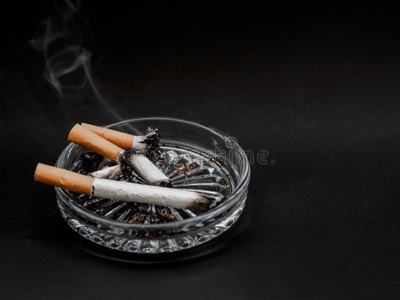 在烟灰缸的香烟在黑背景 烟草 免版税库存照片