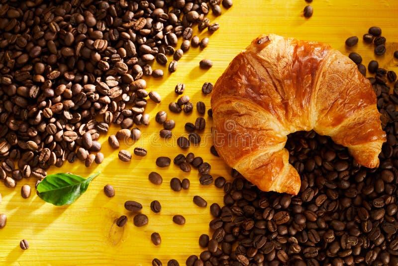 在烤咖啡豆的新鲜的片状新月形面包 免版税库存图片
