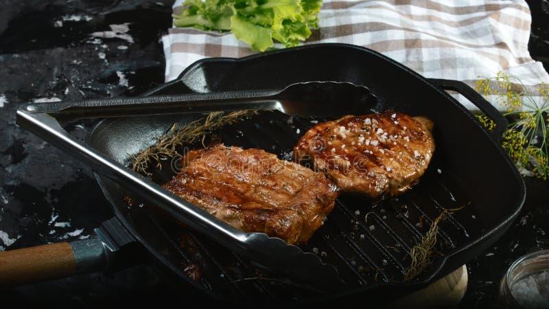 在烤期间的肉 Chuck牛排用草本和香料 在倾吐的餐馆沙拉的主厨概念食物新鲜的厨房油橄榄 图库摄影