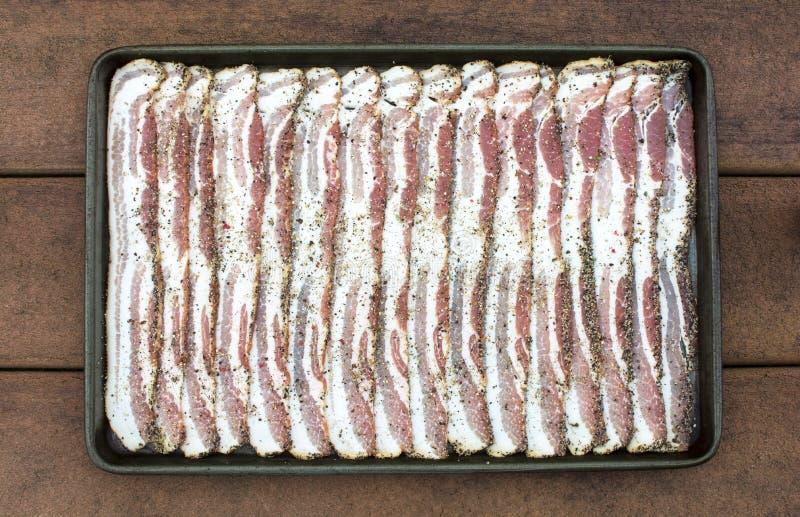 在烤板的未加工的切的干胡椒烟肉 库存照片