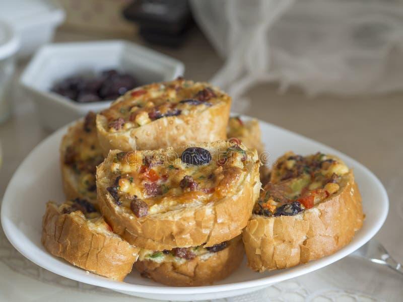 在烤箱和蛋、乳酪、橄榄、蕃茄和香肠片的油煎的早餐面包切片 免版税库存照片