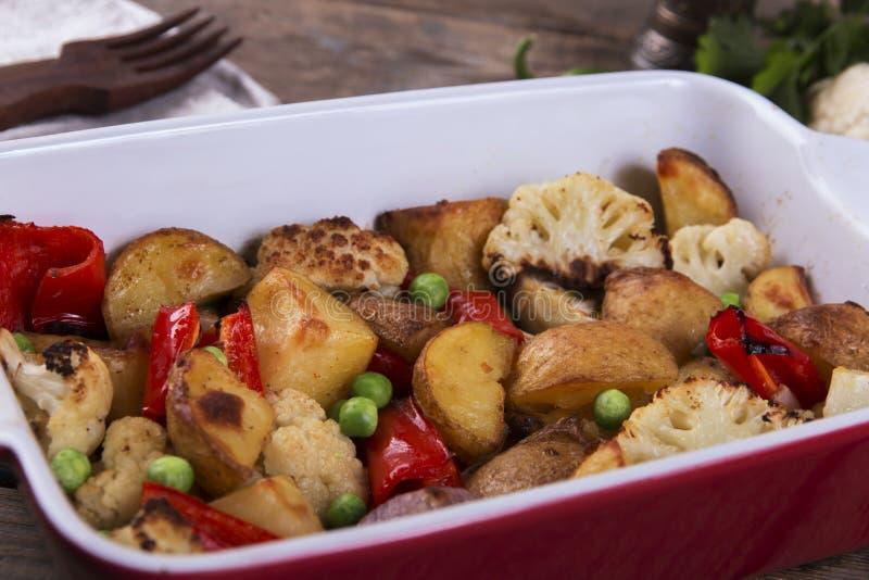 在烤箱土气土豆花椰菜胡椒蔬菜菜肴关闭的被烘烤的菜  免版税库存图片