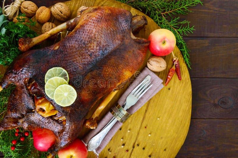 在烤箱烘烤的鹅用苹果 在一个木盘子的圣诞节鹅 免版税库存图片