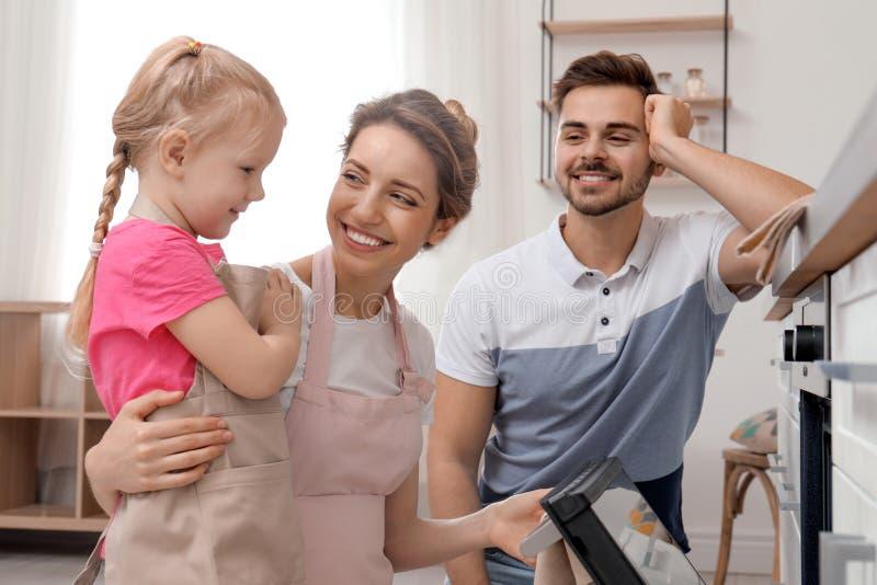 在烤箱的幸福家庭烘烤的食物 免版税图库摄影