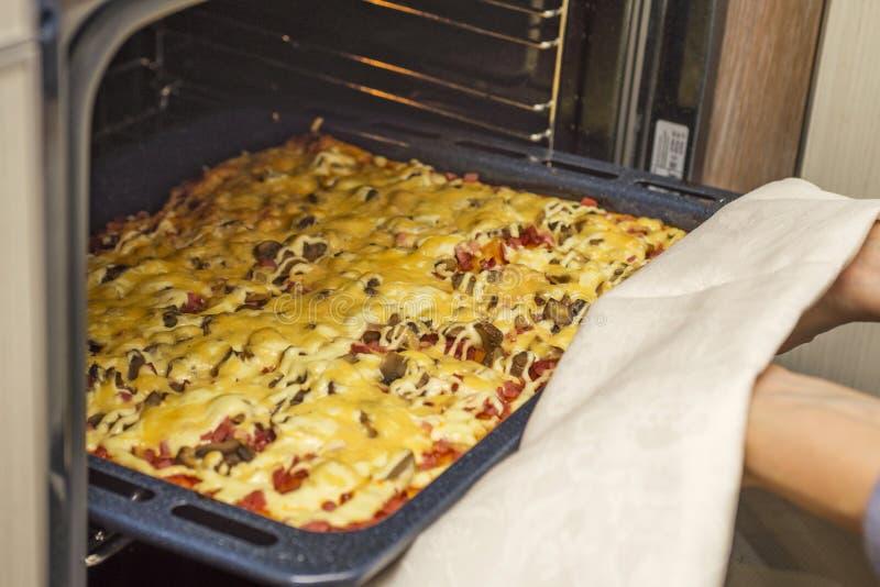 在烤箱的自创辣香肠烘饼 烹调在煤气炉的可口比萨 妇女采取一新鲜的比萨在烤箱外面 库存图片