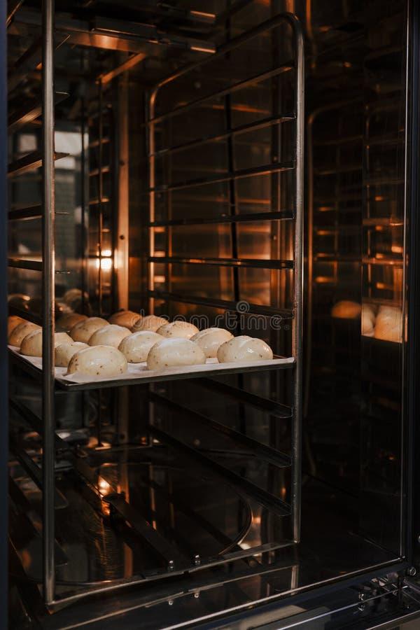 在烤箱的面包烘烤 在面包店的生产烤箱 烘烤的面包 面包制造  免版税库存图片