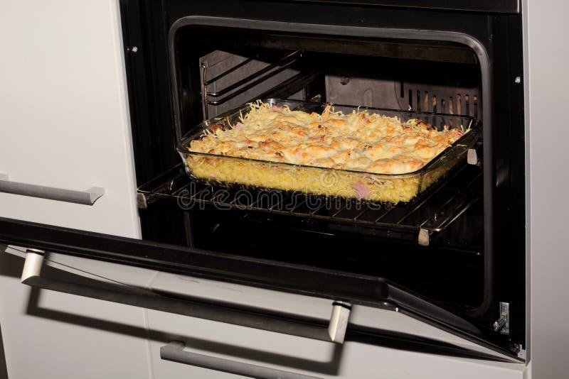 在烤箱的面团、乳酪和火腿焦干酪 免版税库存照片