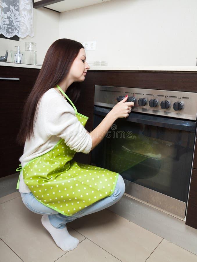 在烤箱附近的女孩 免版税库存图片