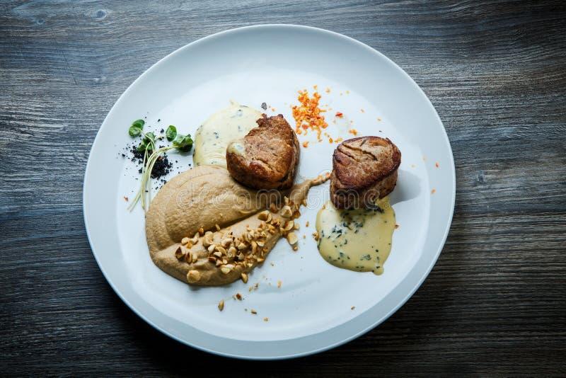 在烤肉两个鲜美片断的顶视图用纯汁浓汤和调味汁 免版税库存照片