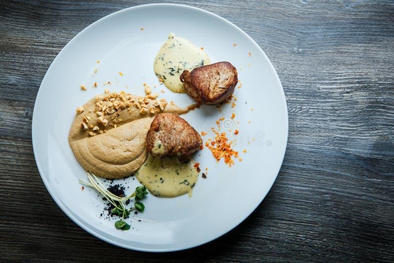 在烤肉两个鲜美片断的顶视图用纯汁浓汤和调味汁 库存照片