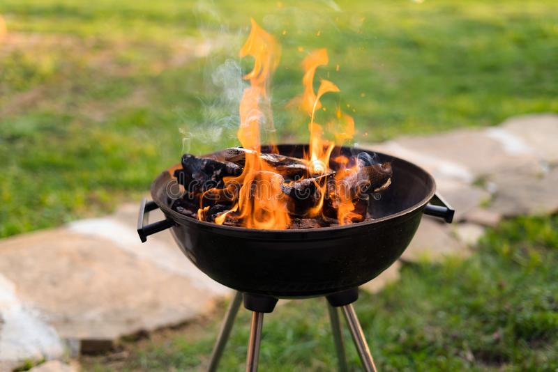 在烤肉格栅的燃烧的木头,热的煤炭为烤肉做准备在后院 浅深度的域 免版税库存照片
