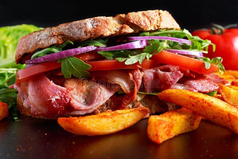 在烤面包的新鲜的自创BLT三明治用烟肉、莴苣、牛肉蕃茄、红洋葱、狂放的火箭和芯片 免版税库存图片