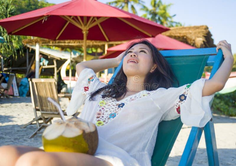 在热带天堂海滩胜地的年轻美丽和愉快的亚洲韩国或中国妇女20s饮用的轻松的椰子汁在su 免版税库存照片