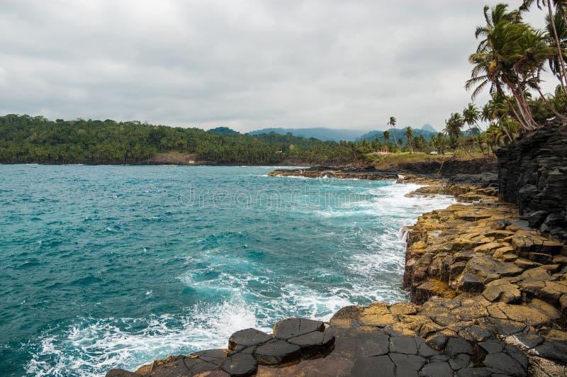 在热带岸的峭壁与棕榈树和原始蓝色海 免版税库存图片