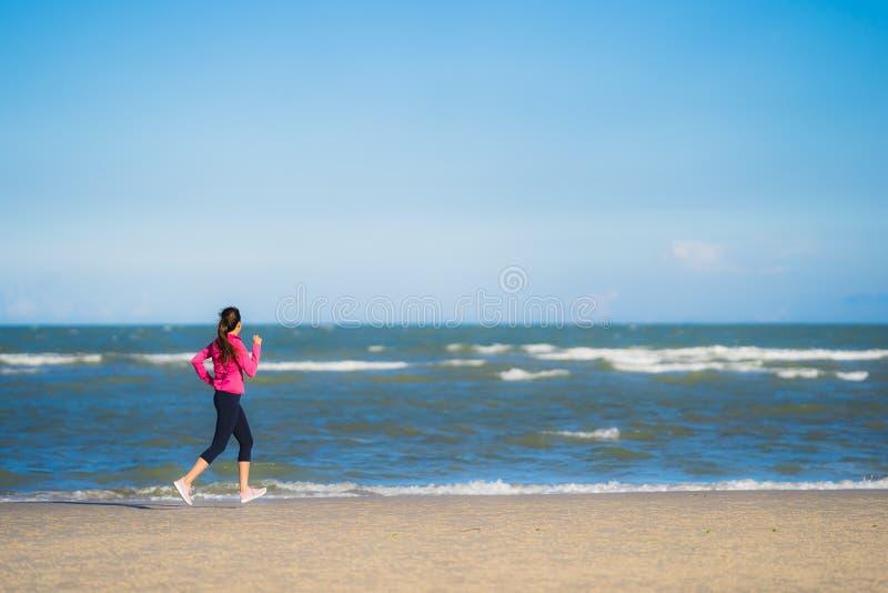 在热带户外自然海滩海上跑步锻炼的美丽亚洲少女肖像 库存图片