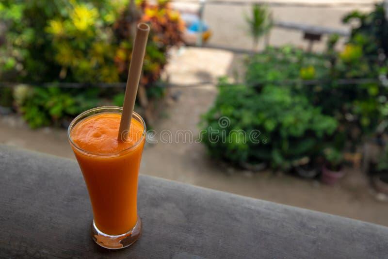 在热带手段阳台的黄色芒果圆滑的人 橙色水果饮料特写镜头照片 刷新的果汁饮料 库存照片